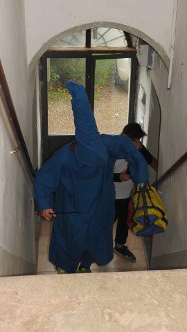 Mago Merlino, vestito di blu con un cappello a punta, sta salendo le scale