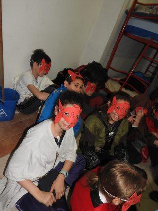 i bambini sono a sedere in una stanza. hanno maschere da pesci in faccia
