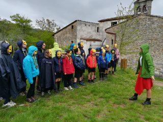i bambini, in fila, hanno delle maschere di uccellinni sulla faccia. di fronte a loro c'è Maga Magò vestita di rosa e rosso.