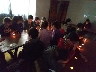 I bambini del branco sono seduti ad un tavolo con lumini accesi davanti. la stanza è buia